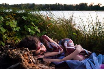 Beautiful freezing woman in bodyart on the autumn river backgrou