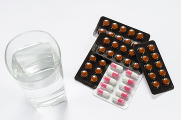 medicines and glass of water on white background