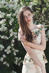 Beautiful young girl model posing near blooming lilacs at spring