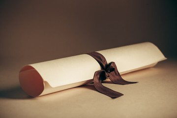 Award. A parchment diploma scroll, rolled up with red ribbon