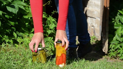 Girl carry out preserved food jars with vegetables from storage