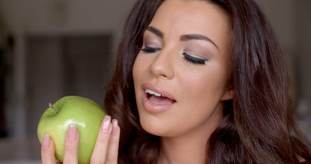 Gorgeous woman eating a healthy green apple
