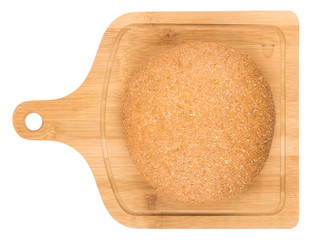 Round bread with bran on bamboo kitchen board