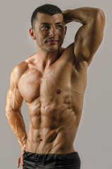 Strong bodybuilder with six pac, shoulders,biceps, triceps,chest