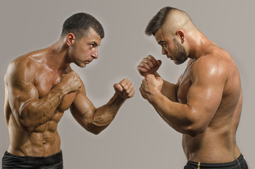Two muscular men fighting, bodybuilders punching each other