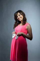 Attractive pregnant woman posing in elegant dress