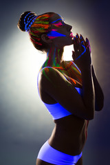 Beautiful slender girl with glowing body art