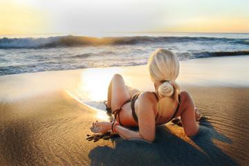 Blonde Frau liegt im Sonnenuntergang am Strand
