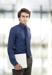 Portrait of young businessman holding laptop
