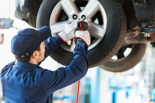 Mechanician changing car wheel in auto repair shop - 80339312