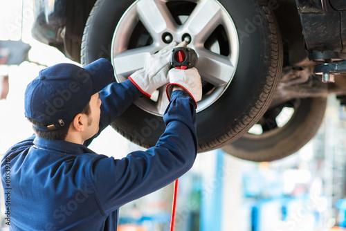Leinwanddruck Bild Mechanician changing car wheel in auto repair shop