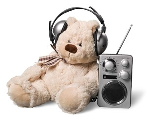 Listen. Retro toy Teddy Bear with headphones and radio receiver