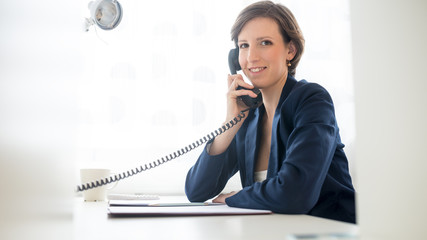 Friendly businesswoman talking on the telephone