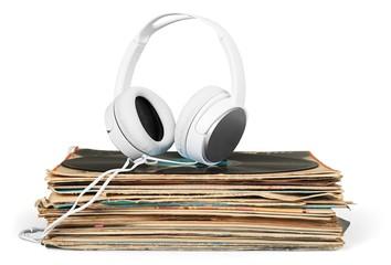 Vinyl. Golden headphones lying on the stack of vinyle records.