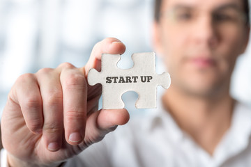 Businessman holding puzzle piece with Start up text