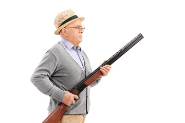 Senior gentleman with hat holding a rifle and standing in a row