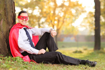 Joyful man in superhero outfit sitting on a grass