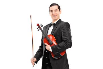 Young confident violinist in black suit holding a wand and a vio