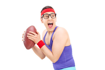 Young nerdy guy in sportswear playing football