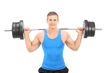 Young smiling athlete in blue shirt exercising with a heavy weig