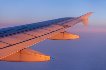 Flight at sunrise. The wing of the plane and the sky