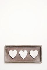 Drei Herzen aus Holz auf weißem Hintergrund im Hochformat