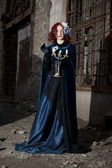 Gothic redhead woman walking with candle