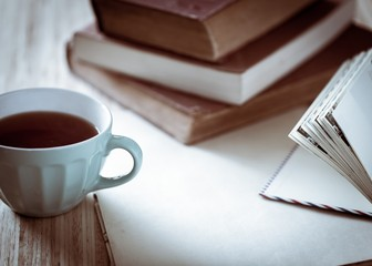 Tea. Books, flowers and white cup on wooden table