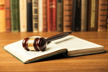 Law. Open law book with a judges gavel resting on top of the
