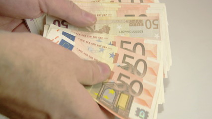 A hand counting lots of 50 Euros