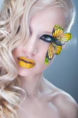 Blonde curly woman with yellow butterfly on lashes