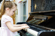 Cute little girl playing old piano - 80344907