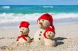 Beach. Snowmen family at sea beach in santa hats. New years and - 80345117