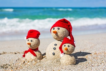 Beach. Snowmen family at sea beach in santa hats. New years and