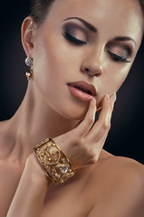Beauty portait of young woman with golden bracelet