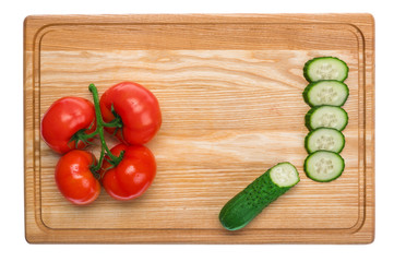 fresh tomatoes and sliced cucumber on a wooden cutting board