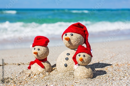 Leinwandbild Motiv Beach. Snowmen family at sea beach in santa hats. New years and