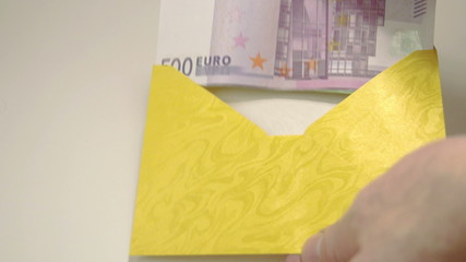 Some Euro bills inside the yellow envelope