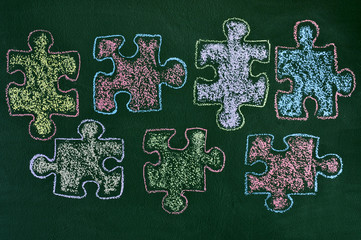 puzzle pieces of different colors drawn on a chalkboard, as the