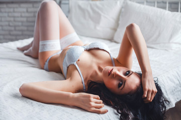Sexy young brunette woman in a white lingerie lying on a bed