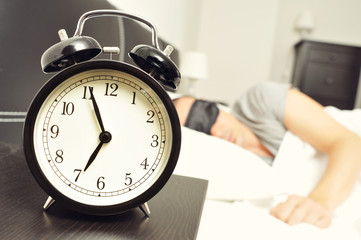 alarm clock and young man sleeping in bed with a sleep mask