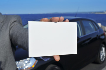 man hand holding a blank signboard with a car in the background