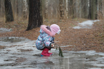 Two years-old toddler girl in warm cloths sitting in icy puddle
