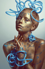 Woman with golden body-art and blue tubes