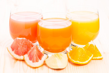 Different juice in glass with pieces of fresh fruits.