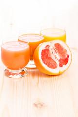 Three glasses of juice with cut in half grapefruit