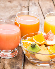 Pieces of fresh fruits in glass bowl with juice