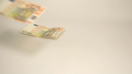 Seven 50 Euro bills dropping on the table