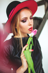 Trendy model in leather black dress and hat with flowers