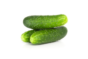 Three fresh cucumbers on a white background..